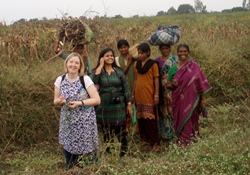 Christian Aid's Rosamond Bennett in a field with local ladies.