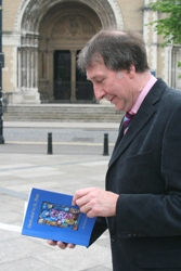 With St Anne's Cathedral in the background, author Duncan Scarlett flicks through his book 'Dedicated to St Anne.'