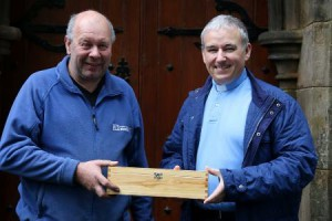 Mr Tommy Dowds, representing Martin and Hamilton Contractors, receiving a time capsule from the Rev Gary Millar which will be place in the church to mark the re-roofing of St Colmanell's Church.