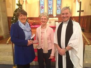 Mrs Rosemary Frayne, organiser of Christmas Tree Festival, and the Rev Gary Millar present a cheque for £7,500 to Mrs Jean Boyce of the NI Hospice.