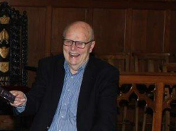Harry Fisher, a former Parish Secretary, was delighted to receive the first copy of the commemorative brochure. Photo: Loraine Watt.