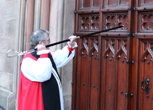 Archbishop John McDowell knocks on the door of St Patrick's Cathedral, Armagh, with his crozier before the Service of Enthronement.