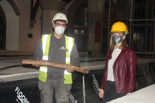 David McClimond shows the Rev Emma Carson, curate in St Patrick's, Ballymena, a piece of charred wood  taken from wall – a remnant of the fire of 1879.  Photo: Loraine Watt.